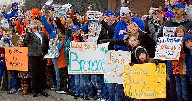 Boise State fans hold out signs as team buses carrying the football team from the airport arrive in downtown Boise on Tuesday.