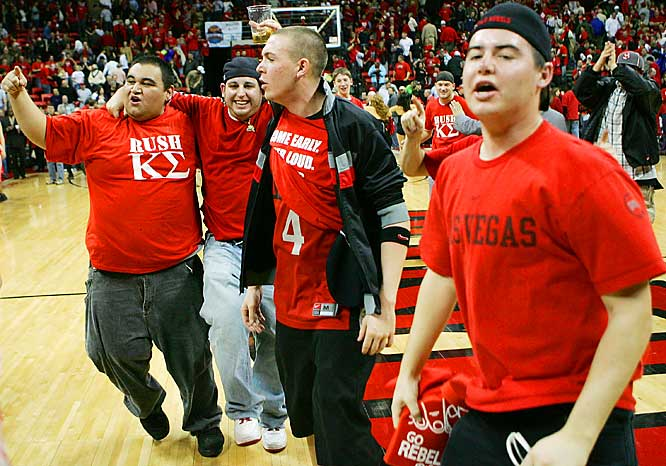 UNLV fans celebrate on the court after the Rebels beat New Mexico, 76-72, in overtime on Saturday.