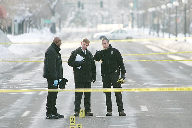 Investigators stand on Speer Blvd., the site of the shooting in Denver that ended Williams' life.