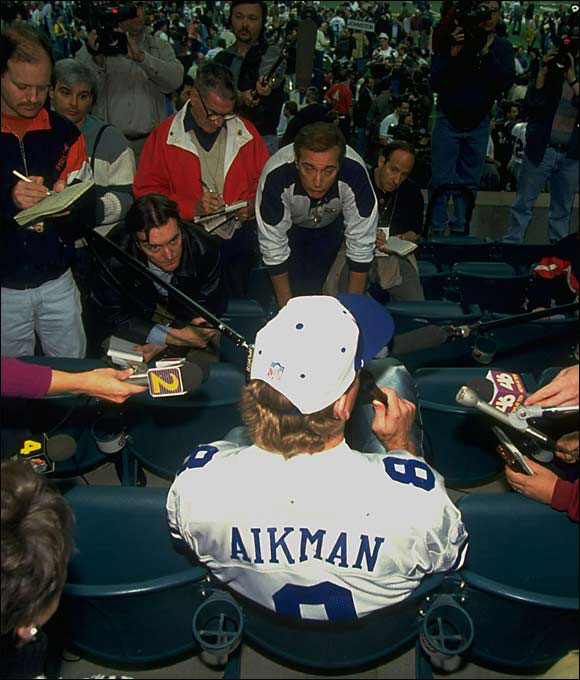 "To Cowboy quarterback Troy Aikman: ""Does it seem a little strange answering football questions in a baseball stadium?"""