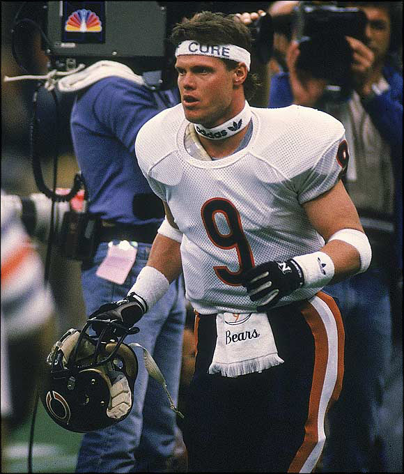 """Bears QB Jim McMahon' reputation as a hellion preceded him. On the heels of a $5,000 fine levied by NFL Commissioner Pete Rozelle for wearing a headband with a sponsor's name on it during Chicago's divisional playoff game, McMahon retaliated by wearing one with """"Rozelle"""" on it during the NFC title game. The feisty QB continued to make headlines in New Orleans by mooning a news helicopter as it hovered over the Bears' practice field."""