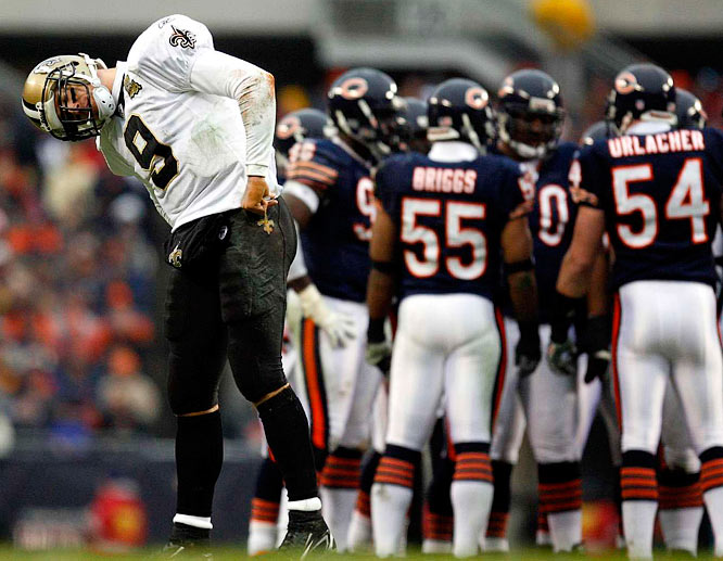 Brees attempts to regain his equilibrium while the Bears defense huddles.