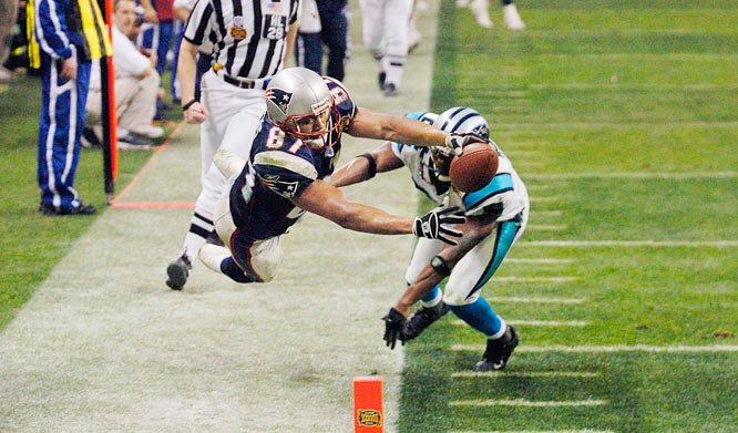 New England wide receiver David Givens (87) makes a catch at the Carolina three-yard  line against  Panthers cornerback Ricky Manning Jr. on third-and-9. The reception set up the Patriots' last TD in the fourth quarter of Super Bowl XXXVIII.