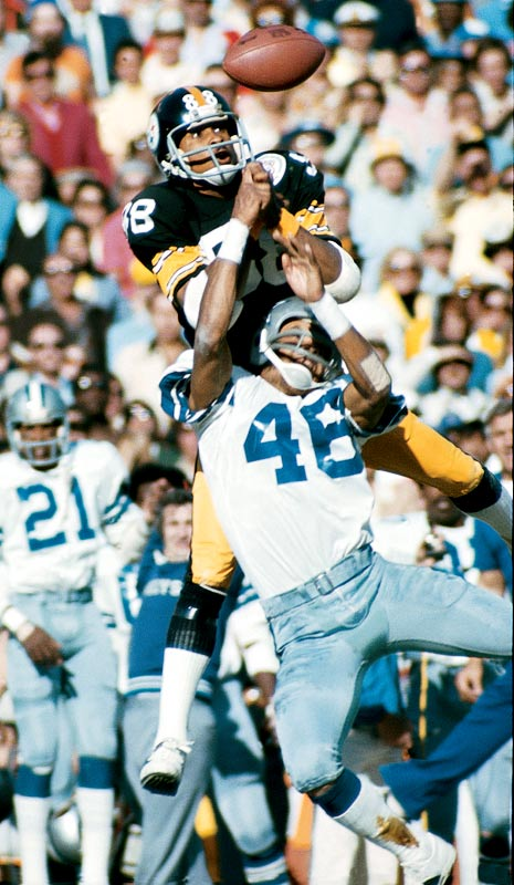 Pittsburgh Steelers wide receiver Lynn Swann making a juggling catch as Dallas Cowboys defensive back Mark Washington (46)  watches. The Steelers defeated  the  Cowboys in Super Bowl X.