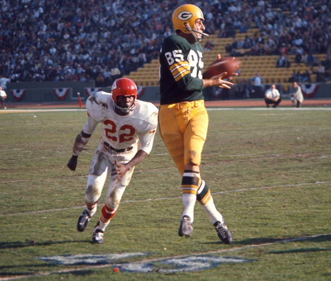 Max McGee of the Green Bay Packers making one of his seven receptions in Super Bowl I in front of Chiefs defensive back Willie Mitchell.  McGee scored two touchdowns in  the Packers'  35-10 victory.