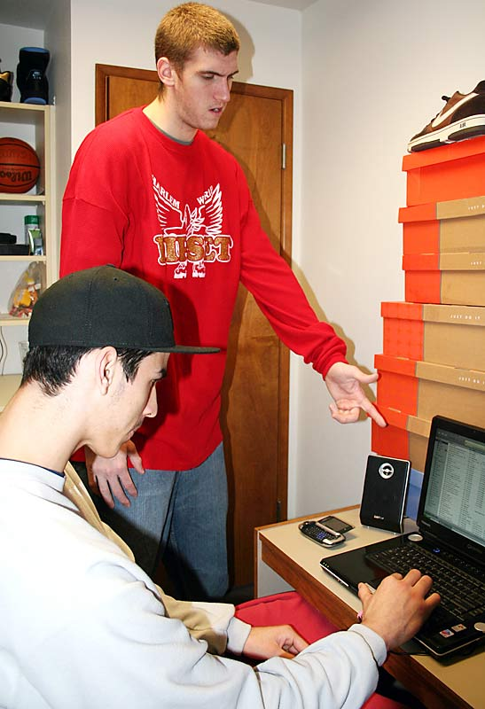 "In Phil's room, Spencer tries to set up an action shot. ""Pick that one!"" he repeats, as our photographer takes a couple shots. With Spencer as a reference point, that tower of shoe boxes must be nearly seven feet tall -- apparently both are avid collectors of the foot wear."