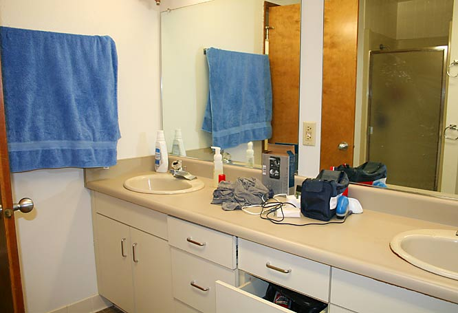 Here's the bathroom. Two showers, two toilets and lots of space. It's pretty clean, but that shower- head looks awfully short for the tallest guy on campus.