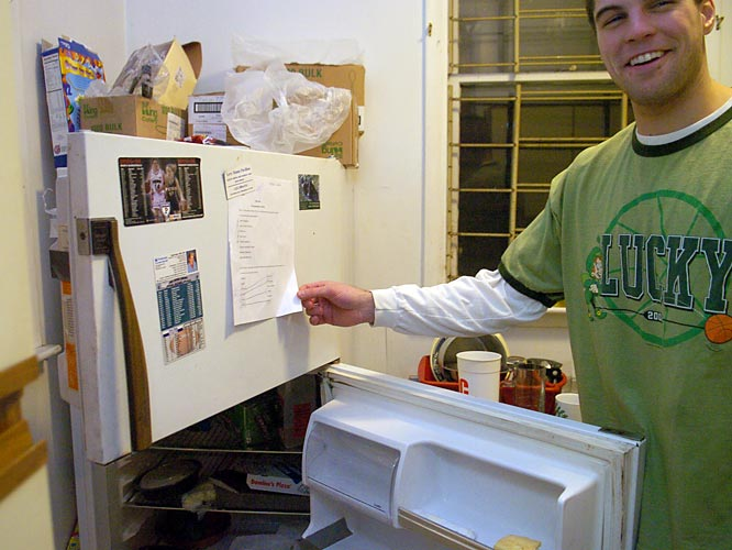 Like many college students, the refrigerator's main use is to store leftover remnants of takeout food. But as Mark shows, they do use it for at least one other purpose. In a throwback to elementary school, Mike's quiz (which he received an 97 percent on) is hung prominently for everyone to see.
