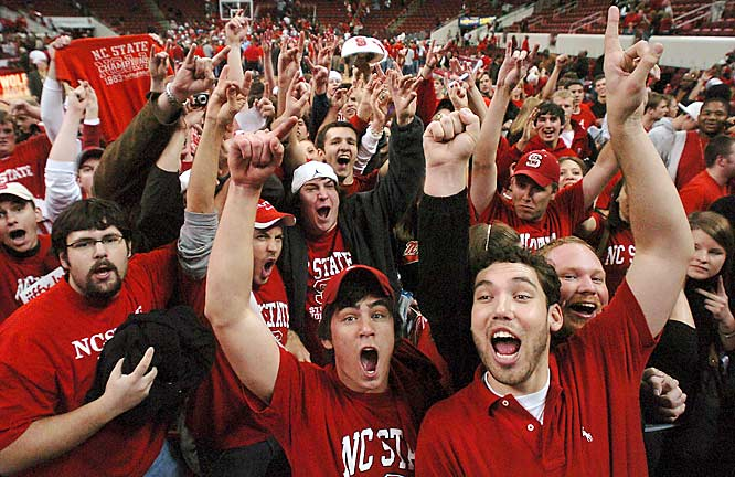 NC State fans storm the court after the Wolfpack upset No. 3 North Carolina, 83-79, on Saturday.
