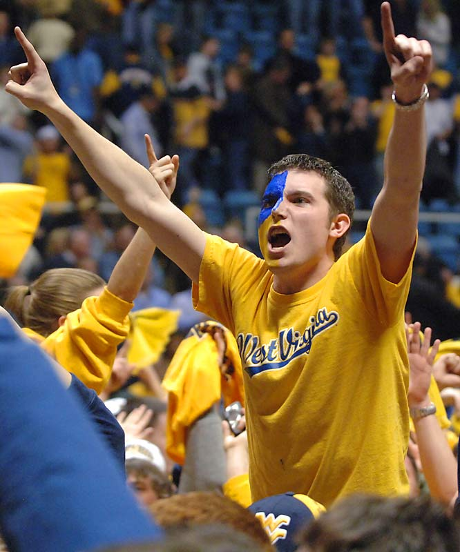 A West Virginia student takes the floor to celebrate after the Mountaineers 70-65 upest over No. 2 UCLA on Saturday.