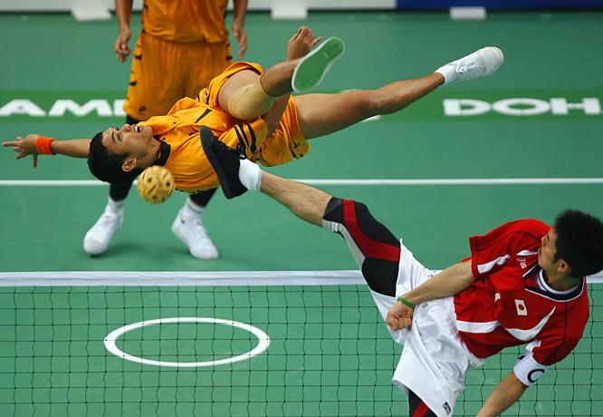 Mohd Azlan Abdul Mubin (orange) of Malaysia against Japan's Susumu Teramoto (red) during the men's Sepaktakraw team preliminaries.