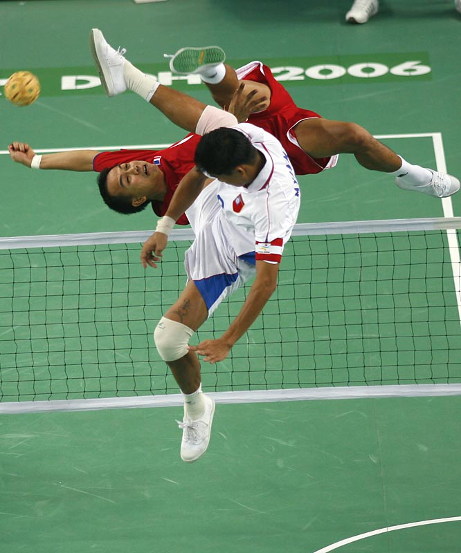 Aung Cho Myint U of Myanmar (white) and Thailand's Singha Somsakul (red) competing  in the men's Sepaktakraw  team semifinal.