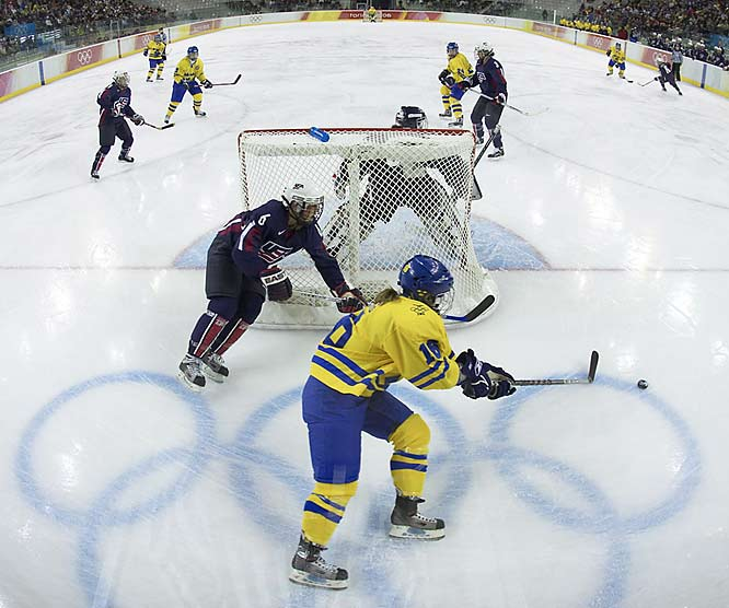 "Klutho's take:<br><br>""I like this view. It's the view above the goal judge, which I captured using a fish-eye lens. You can see the whole ice surface. The Olympic rings make a good element in the bottom of the frame. There's action behind the net and then smatterings of players going up the ice.""<br><br> Shot with a Canon EOS-1D Mark II"