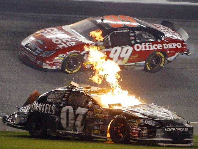 Flames spew from Clint Bowyer's car while Carl Edwards passes on the high side during the last lap of the Daytona 500.