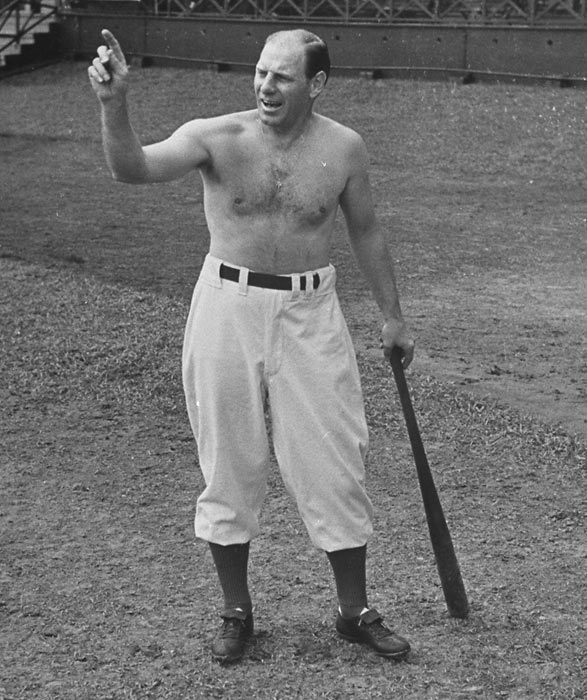 Brooklyn Dodgers manager Leo Durocher opts for the no-shirt look as he gives hitting advice.