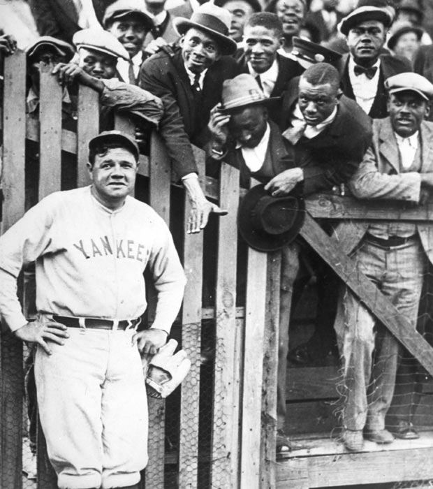 Fans clamor to speak with Babe Ruth as he poses along the outfield fence.