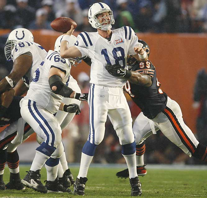 Peyton Manning withstands a heavy rush before throwing a first-quarter touchdown to Reggie Wayne.
