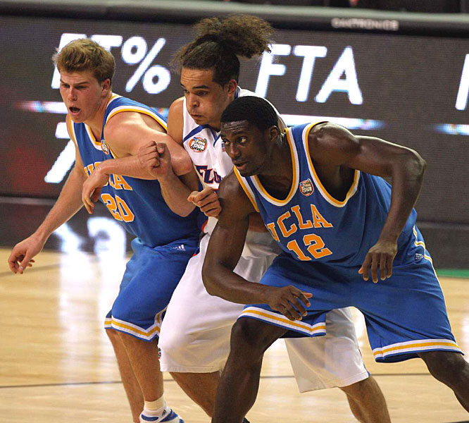 UCLA's Michael Roll, left, and Alfred Aboya sandwich Joakim Noah while fighting for a rebound.