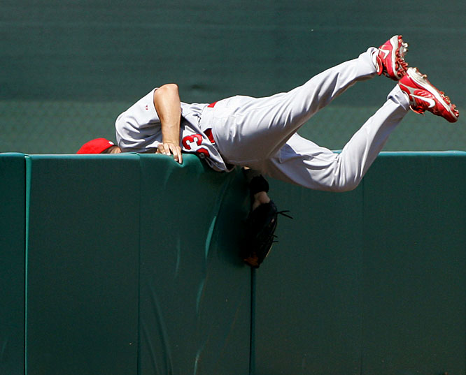 Left fielder Ryan Ludwick hangs on as he slams into the wall chasing a foul ball hit by the Twins' Joe Mauer on March 13 in Fort Myers, Fla.