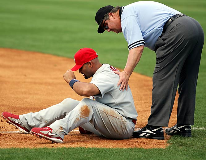 First base umpire Joe West checks on Albert Pujols after the two collided during a game on March 6 in Ft. Lauderdale, Fla.