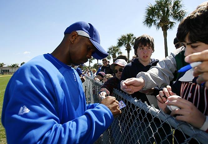 New centerfielder Juan Pierre signs autographs for fans.