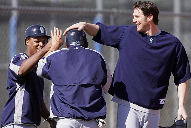 Adrián Béltre, left, and Richie Sexson, right, congratulate Raúl Ibañez on scoring a run during practice.