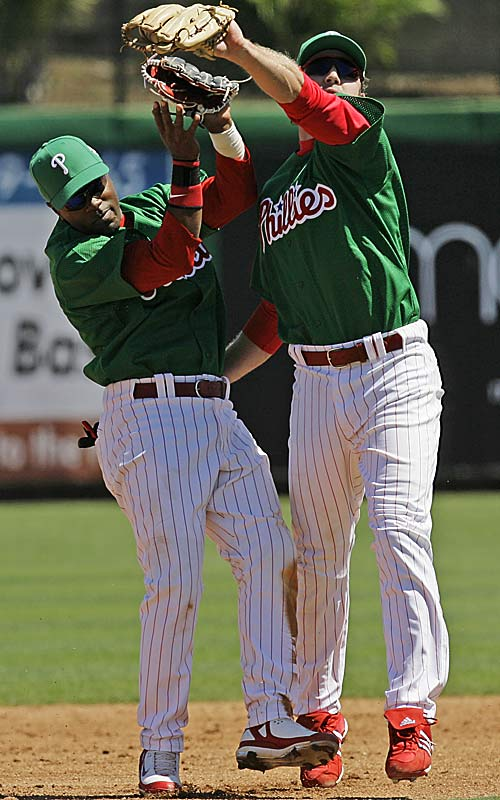 In the spirit of St. Patrick's Day, Chase Utley and Jimmy Rollins collide in green uniforms as Utley fields a fly out.