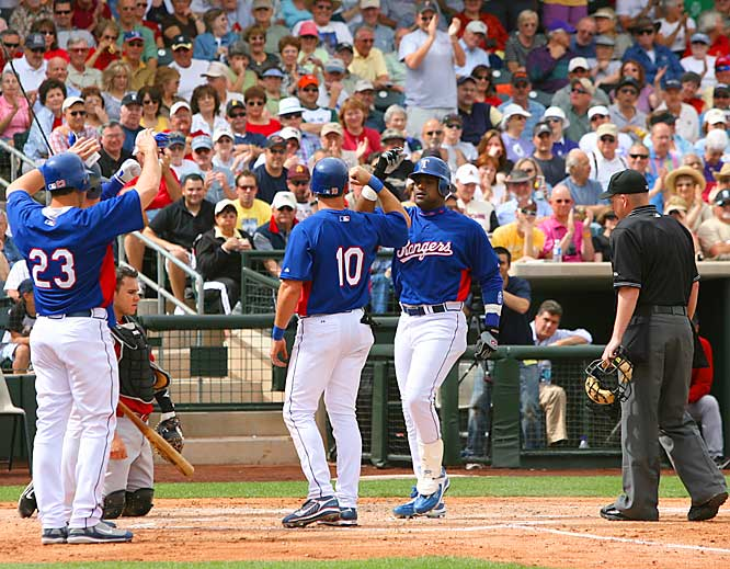 Mark Teixeira (23), Michael Young (10) and Sosa meet at home plate after a home run.