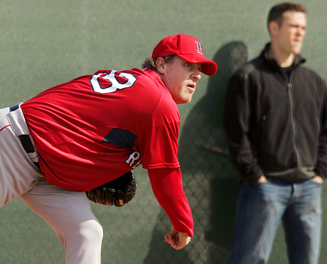 Curt Schilling gets loose as GM Theo Epstein looks on. The veteran right-hander had asked for a contract extension for 2008 only to be rejected by management.