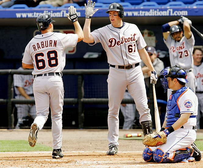 Right fielder Ryan Raburn, left, high-fives teammate Mike Hessman after his second inning solo-home run against the Mets at Tradition Field in Port St. Lucie, Fla., in the major-league exhibition opener for both clubs.