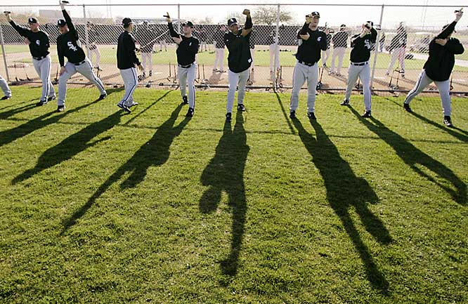 Players cast long shadows as they go through morning stretching exercises.