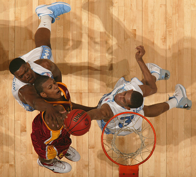 In a different angle of the previous image, USC's Nick Young fights for the ball against two North Carolina players.