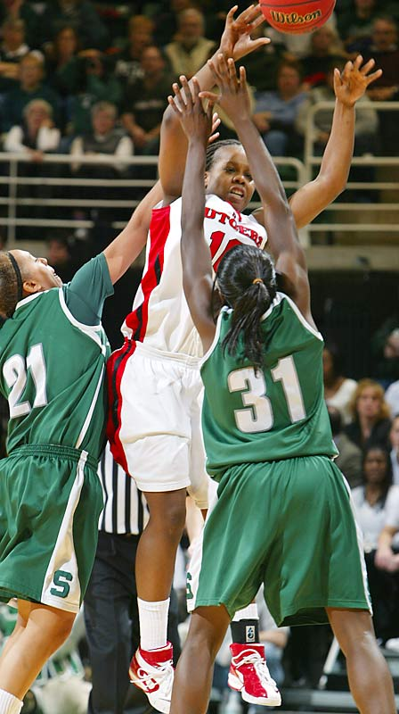 Rutgers Epiphanny Prince barely escapes a trap from Michigan State's Mia Johnson (No. 21) and Victoria-Lucas Perry (No. 31). The Scarlet Knights defeated the Spartans, 70-57, to advance to the Sweet 16.