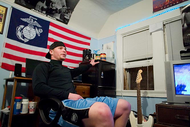 Olson reclines in his third-floor bedroom in front of a US flag honoring his brother, who just finished serving in the Marines.