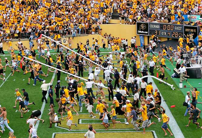 Colorado fans storm the field as security officials lower the goal posts after the Buffaloes defeated Colorado State on a 47-yard field goal in September 2005.