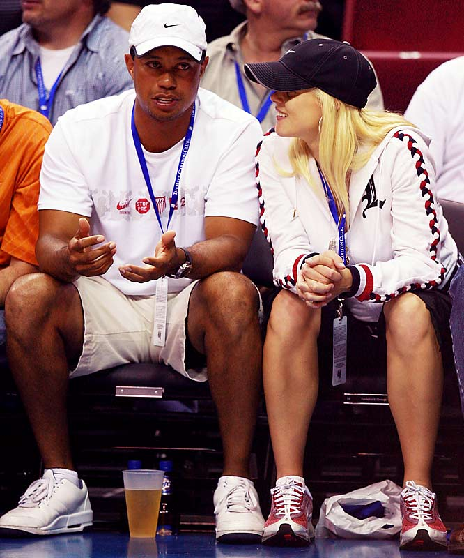 Tiger Woods, shown here at a Magic-Pistons playoff game, explains to his wife, Elin, that it wasn't that difficult for him to get front-row tickets.