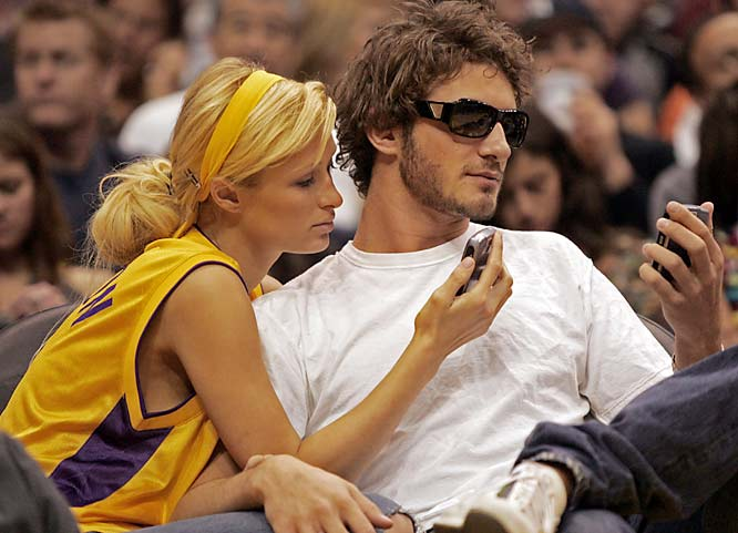 Paris Hilton and her on-off playmate, Greek shipping heir Stavros Niarchos, stare intently at their cell phones during a break in the action at a Lakers' game.