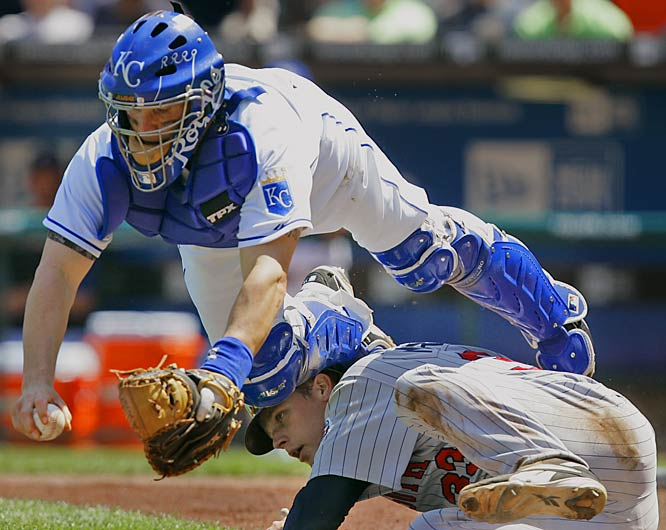 Royals' catcher Jason LaRue falls over the Twins' Justin Morneau after tagging him out in the fourth inning on Saturday.  The Twins won 7-5.