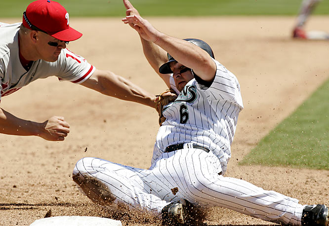 Phillies' third baseman Wes Helms tags out the Marlins' Dan Uggla in the third inning of a 6-4 win for Florida on Sunday.