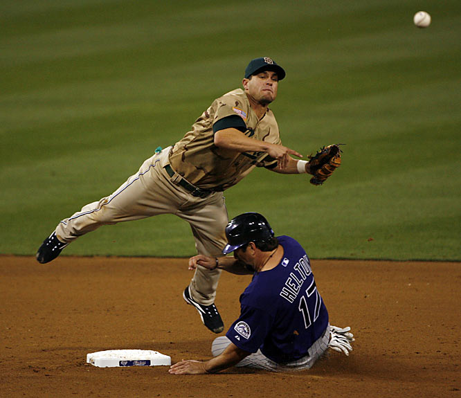 Padres' second baseman Marcus Giles turns a double play in the ninth inning as the Rockies' Todd Helton upends him Saturday, April 7. The Padres went on to win in the bottom of the ninth, 3-2.
