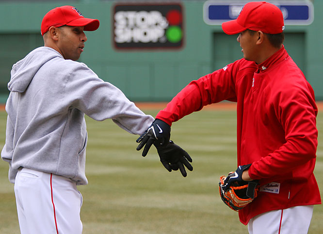 Red Sox pitcher Daisuke Matsuzaka learns a new handshake from Alex Cora before their home opener against the Mariners on April 10.