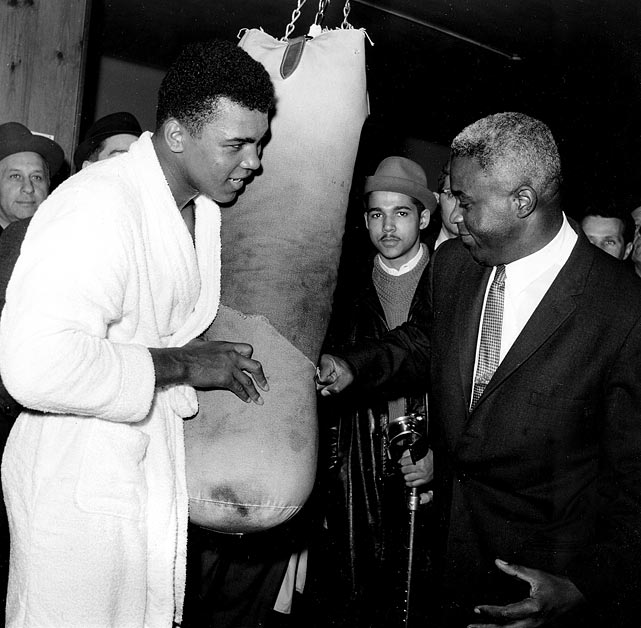 Robinson hits a punching bag held by Cassius Clay in a New York gym in March 1963. Less than a year later, Clay would win the world heavyweight title with a victory over Sonny Liston.