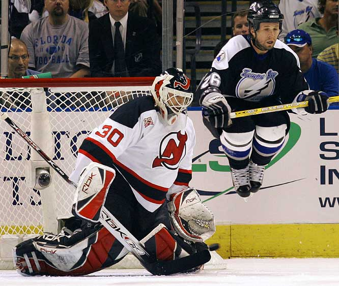 Martin Brodeur makes a save despite Lightning forward Martin St. Louis's attempt to screen him.  Brodeur stopped 32 shots for the Devils, who will face the Senators in the semifinals after winning their series with the Lightning 4-2.