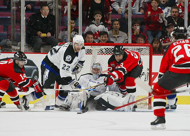 Lightning goalie Johan Holmqvist watches defenseman Dan Boyle attempt to clear the puck away from Devils' forwards Brian Gionta (14) and Scott Gomez (23).
