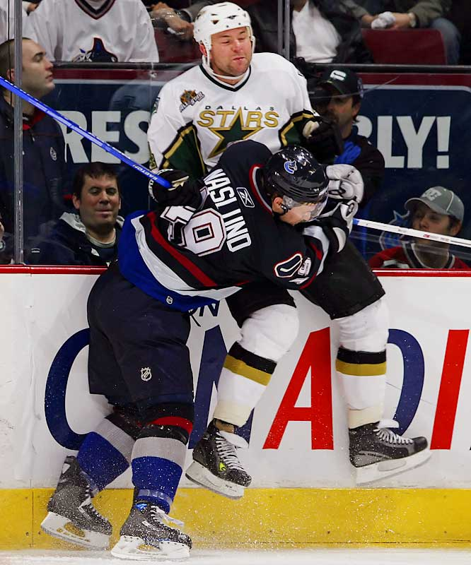 Canucks winger Markus Naslund checks Stars defenseman and fellow Swede Mattias Norstrom hard into the boards.