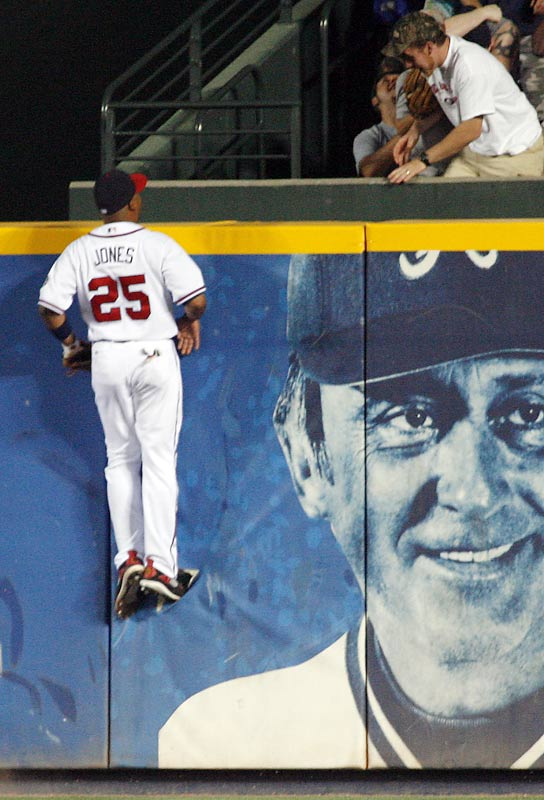 Atlanta center fielder Andruw Jones tries to hide from former Brave Phil Niekro.