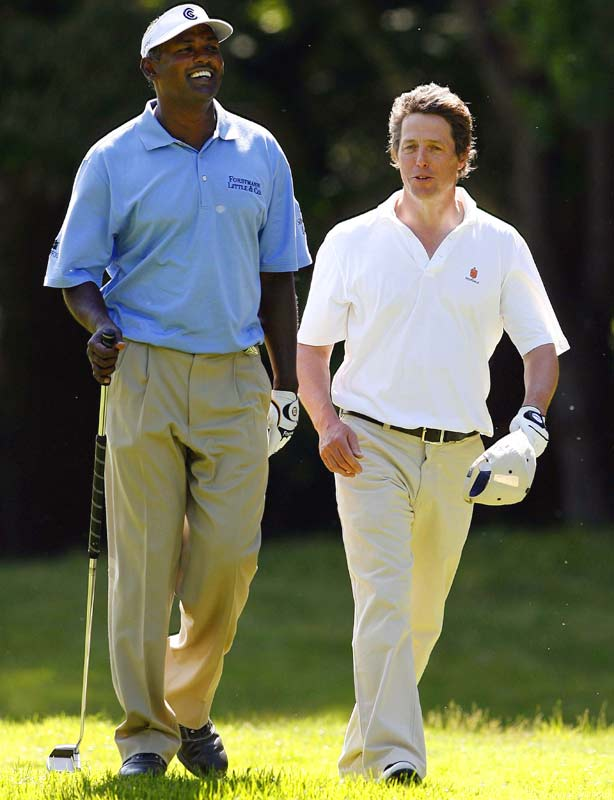 Hugh Grant gets some tips from Vijay Singh during this week's BMW PGA Championship pro am.
