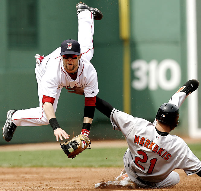 Boston second baseman Dustin Pedroia is upended by Baltimore's Nick Markakis while turning a double play on May 12. The Red Sox resumed their domination of the Orioles with a 13-4 win Saturday.