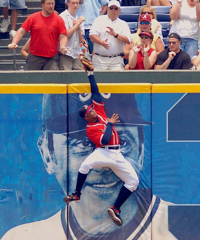 Braves centerfielder Andruw Jones robs the Phillies' Greg Dobbs of a homer in the third inning Sunday. Philadelphia won 13-6.