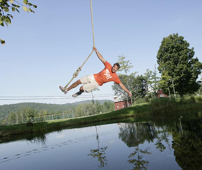 "SIMON SAYS:   ""This is Bode Miller at his dad's farm in New Hampshire. I'd been up there for a couple of days, scouting for a place to shoot. I saw this rope swing over a pond and thought this would be an excellent `Bode being adventurous' photograph. When we did the shoot there were several people there watching, including Bode's agents, handlers, family members, Nike people. So he swings out a couple times, but he has his hand across his face. I say, `Hey, Bode, you've got to be a bit more adventurous.' On this photograph, he swings out and I take the picture. Next thing I know, Bode's coming straight at me, so I fall on the ground and he hits the oak tree behind me. There's silence. But he was fine. In fact he got back out there and did it a couple more times.""  Shot with a Canon EOS-1D Mark II N, EF 16-35mm f/2.8L USM"